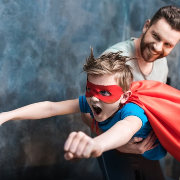 Inspirational Dad holding kid with hero outfit on